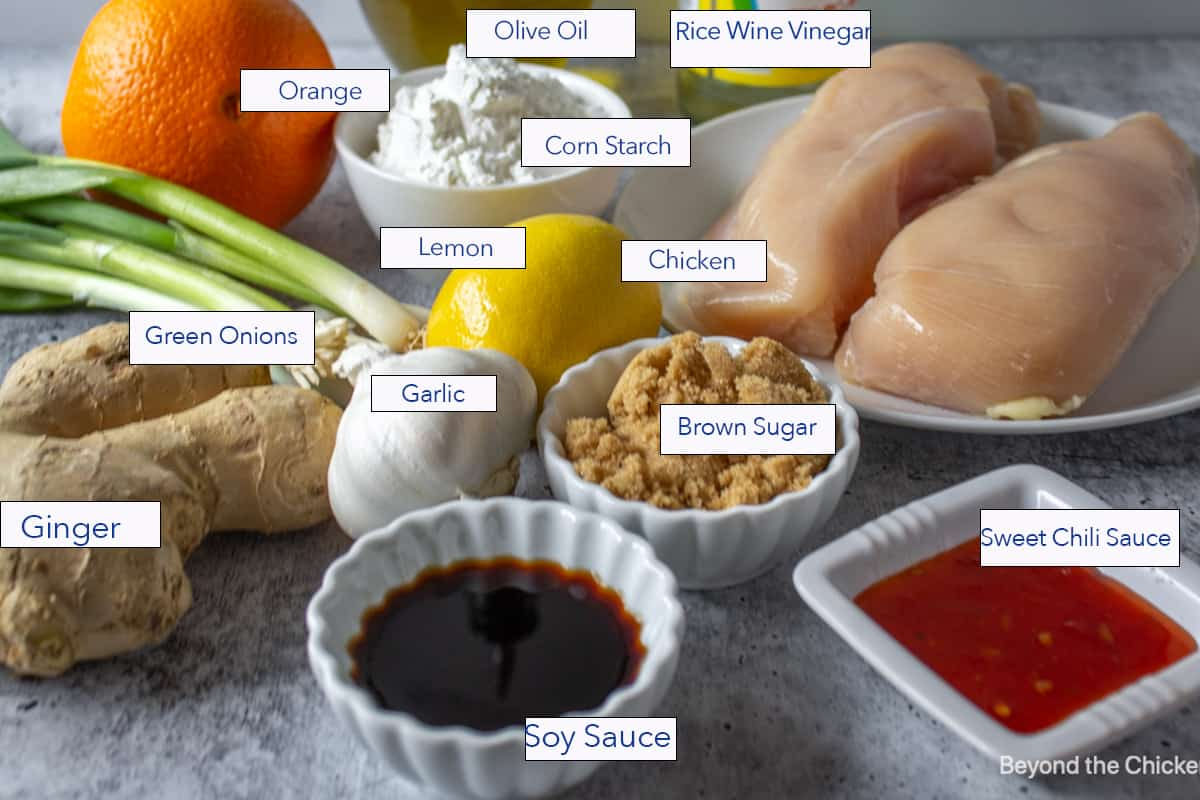 Raw chicken breasts on a plate along with small bowls of ingredients.