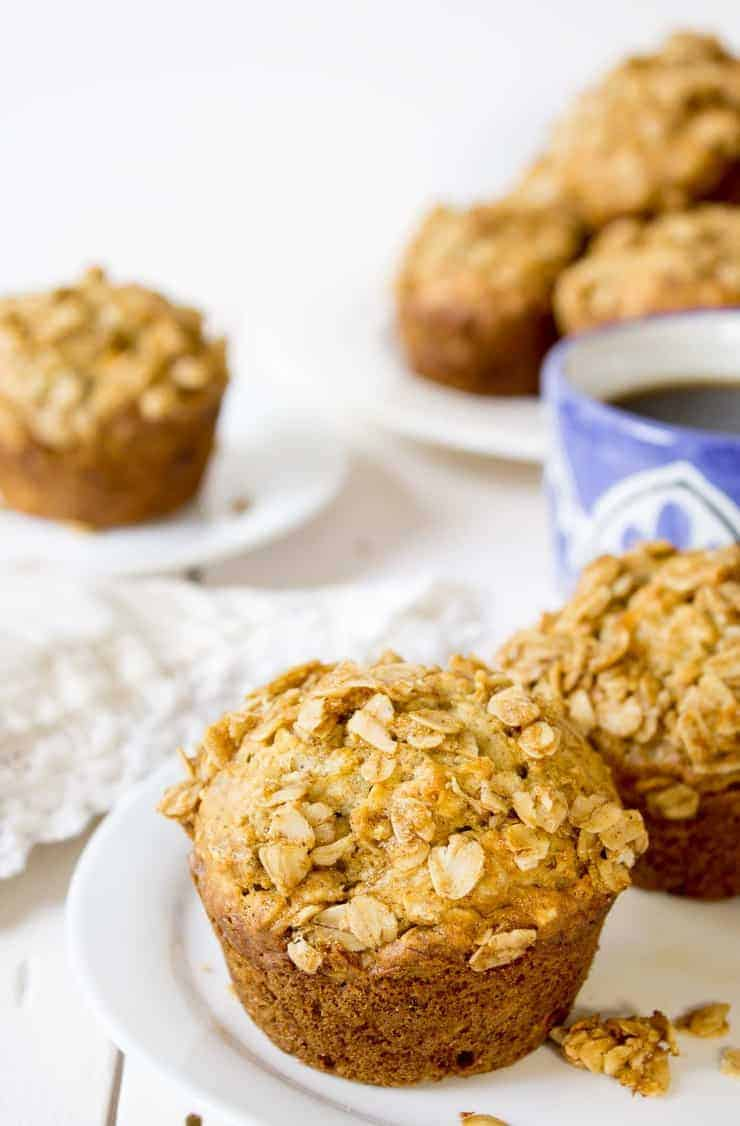 Banana muffins topped with oats sitting on a white plate.