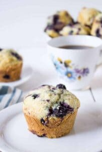 A muffin with blueberries on a small white plate with a teacup in the background.