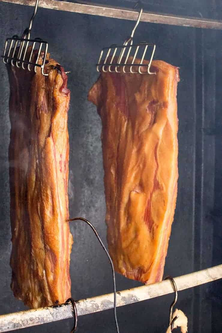 Bacon smoking in a smoker.