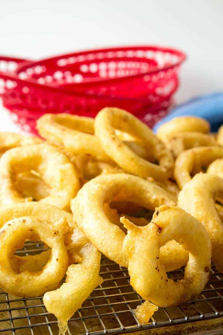 Crunchy, crispy onion rings on a baking rack.