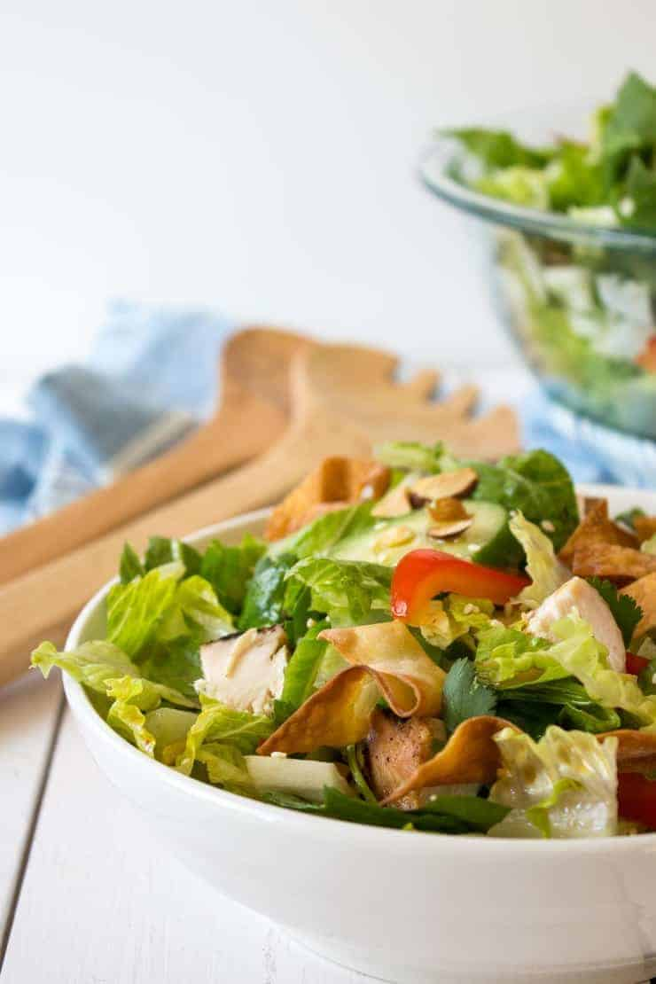 A bowl filled with a salad topped with chicken and bell peppers.