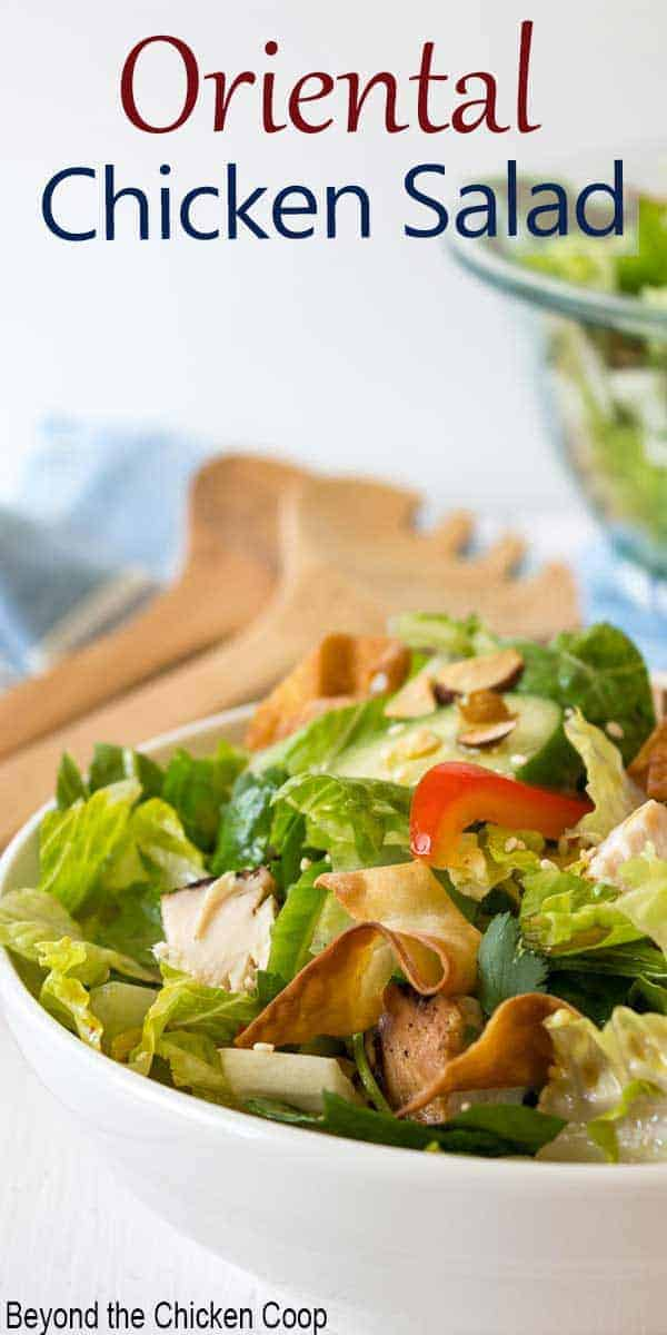 Salad in a white bowl with a pair of wooden spoons next to bowl.