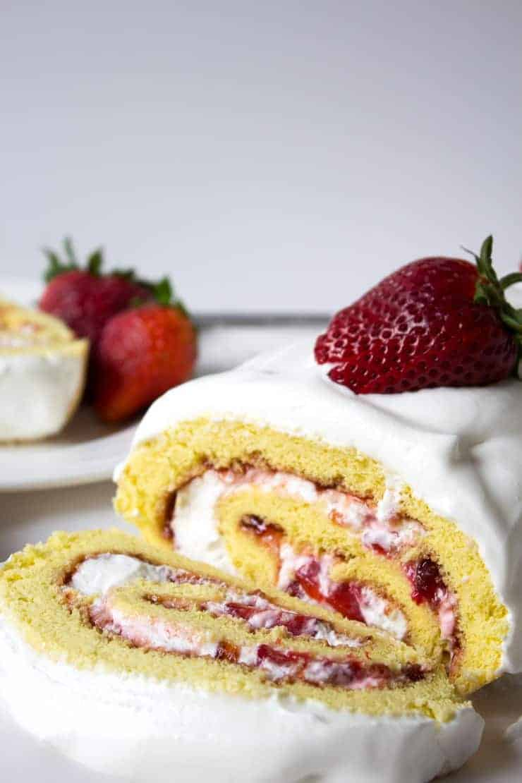 Fresh strawberry filled cake sliced and topped with fresh strawberries.