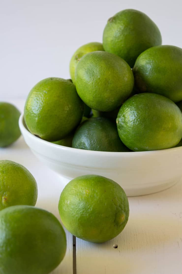 Fresh limes in a white bowl and on a white board.