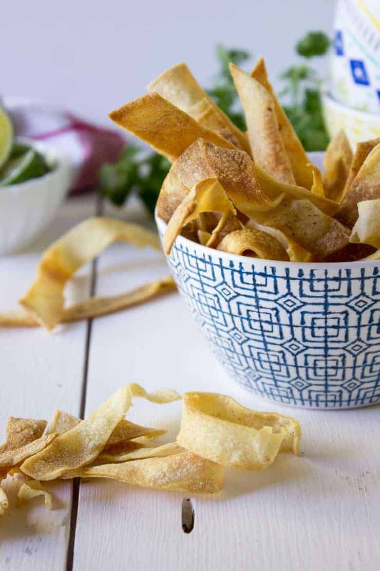 Crispy corn tortillas strips piled on a white board and in a blue patterned bowl.