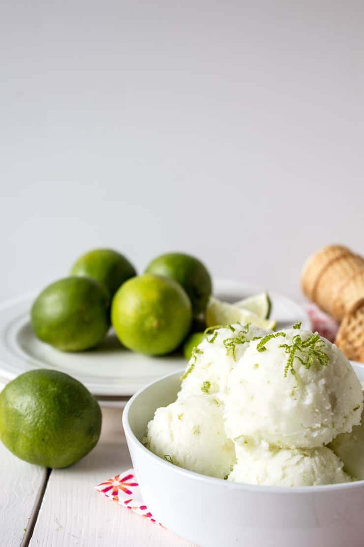 Fresh limes behind a bowl of lime sherbet.