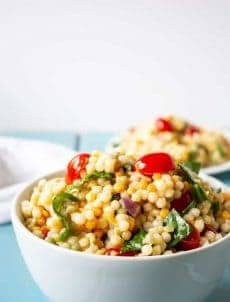 Israeli Couscous salad with spinach, tomatoes and a light orange vinaigrette.