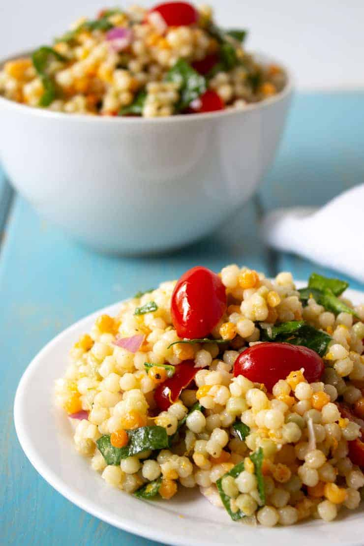 Pearl couscous salad filled with fresh spinach and tomatoes.