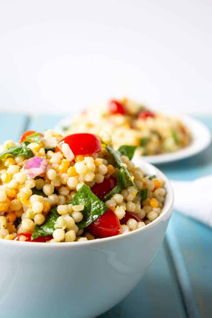 Pearl couscous with spinach, tomatoes and a light dressing.