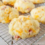 Biscuits with ham and cheese on a baking rack.