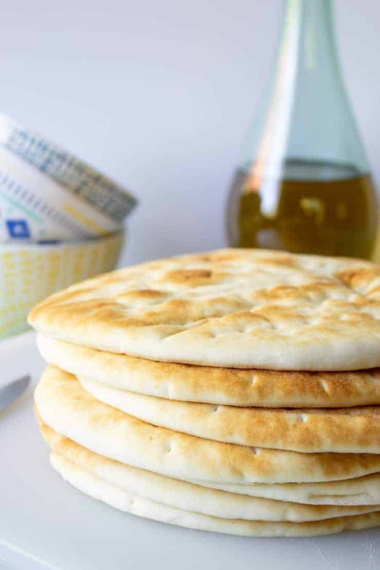 A stack of flat bread and a bottle of olive oil in the background.