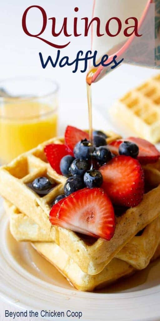 Syrup pouring onto waffles with fresh fruit.