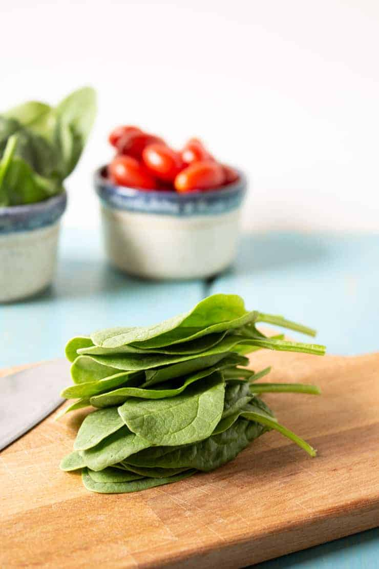 Fresh spinach leaves piled on a cutting board.