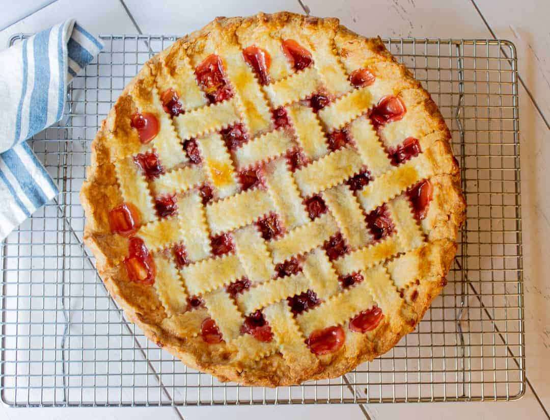 Homemade Cherry Pie with a lattice crust on a baking rack.