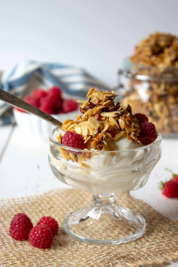Homemade granola piled on a bowl of yogurt and served with fresh raspberries.