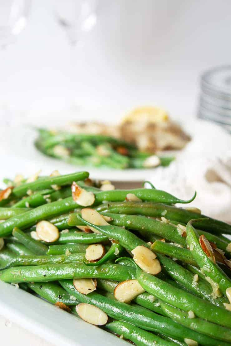 Green beans on a platter with sliced almonds.