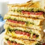 A stacked grilled cheese sandwich with pesto and tomatoes.