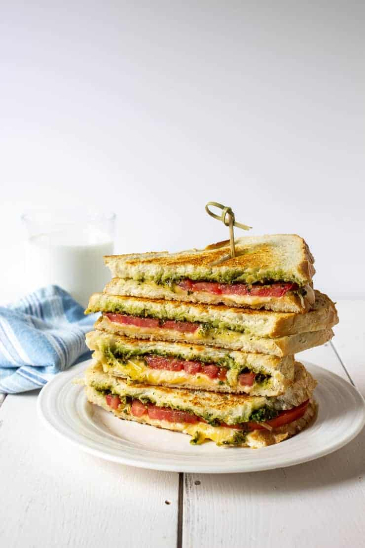 Pesto and tomato grilled cheese sandwich stacked on a plate