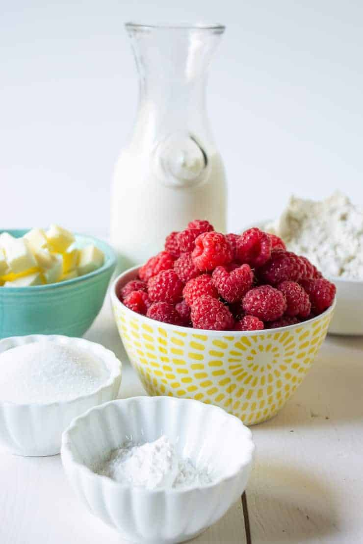 Fresh raspberries in a bowl along with flour, sugar, butter, milk and baking powder.