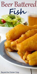 Fillets of beer battered fish on a blue and white plate.