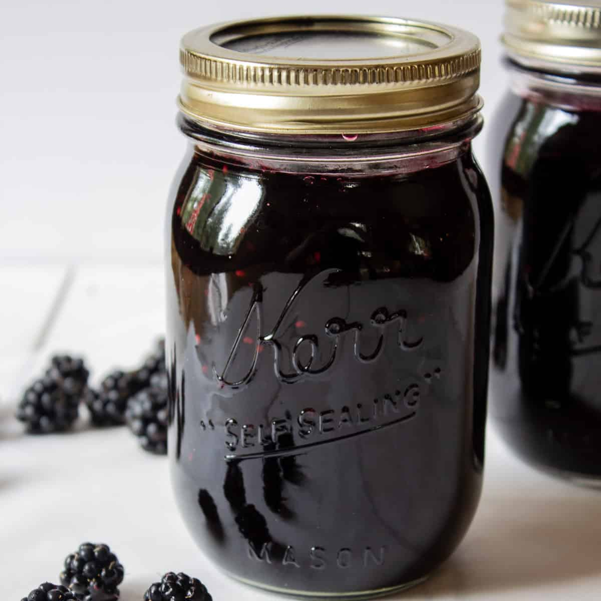 A glass canning jar filled with blackberry jam.
