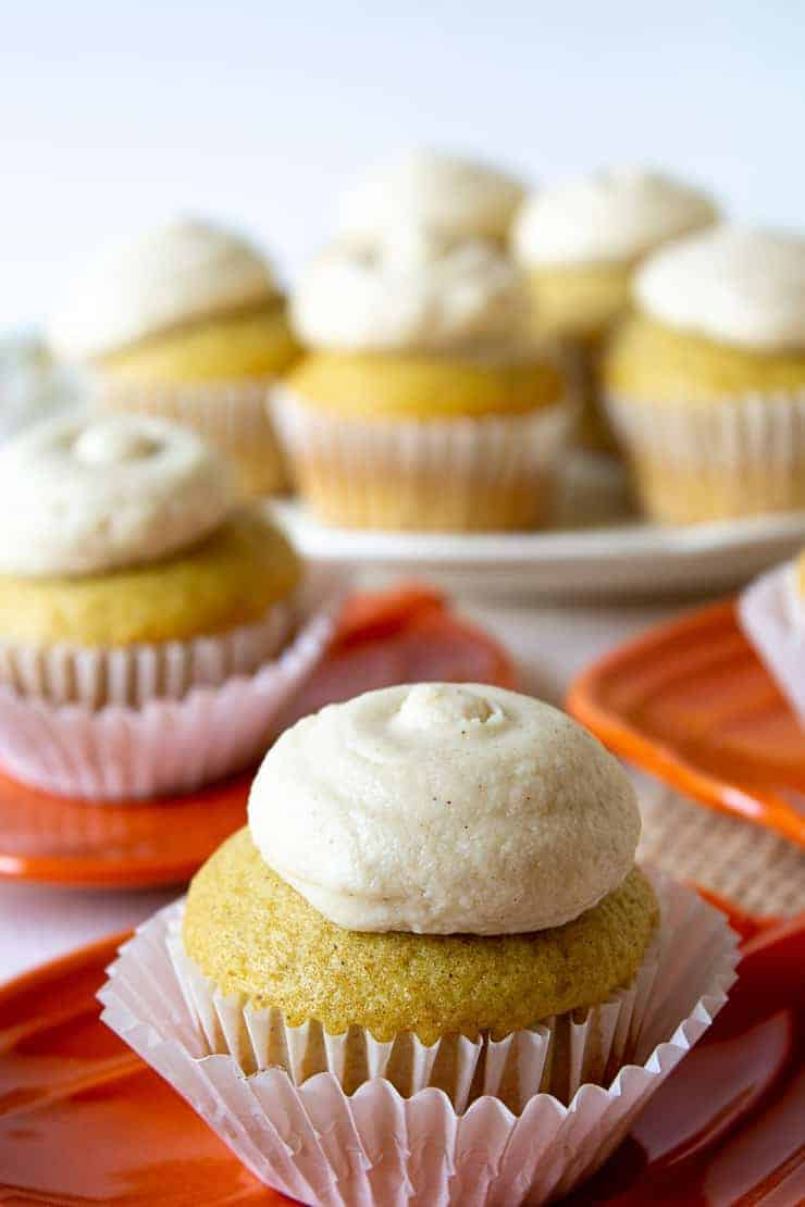 Yellow cupcakes topped with a dollop of frosting.