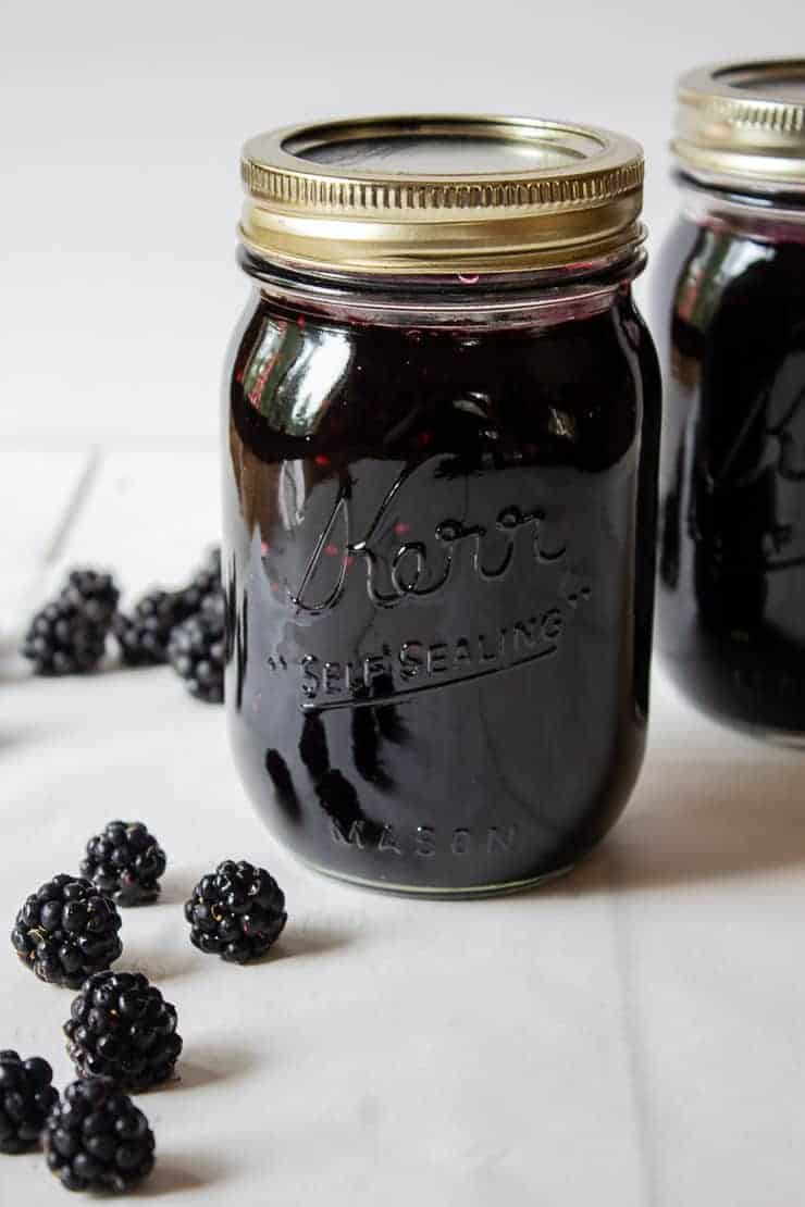 Homemade jam in canning jars with fresh blackberries