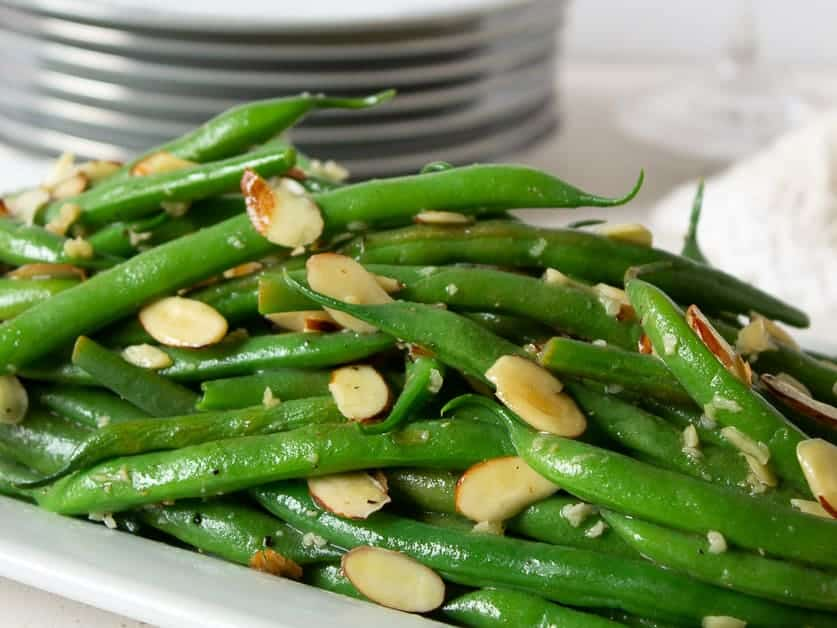 Cooked green beans topped with sliced almonds.