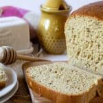 A loaf of bread cut with honey and butter next to the bread.