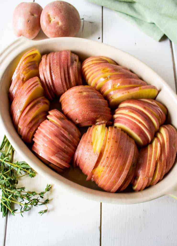 A casserole dish filled with sliced potatoes for roasted hasselback potatoes.