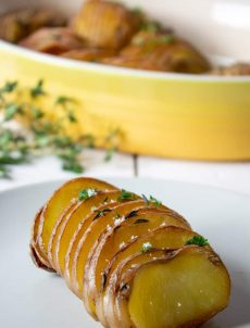 Roasted Hasselback potatoes with a sprinkle of coarse salt and fresh herbs.