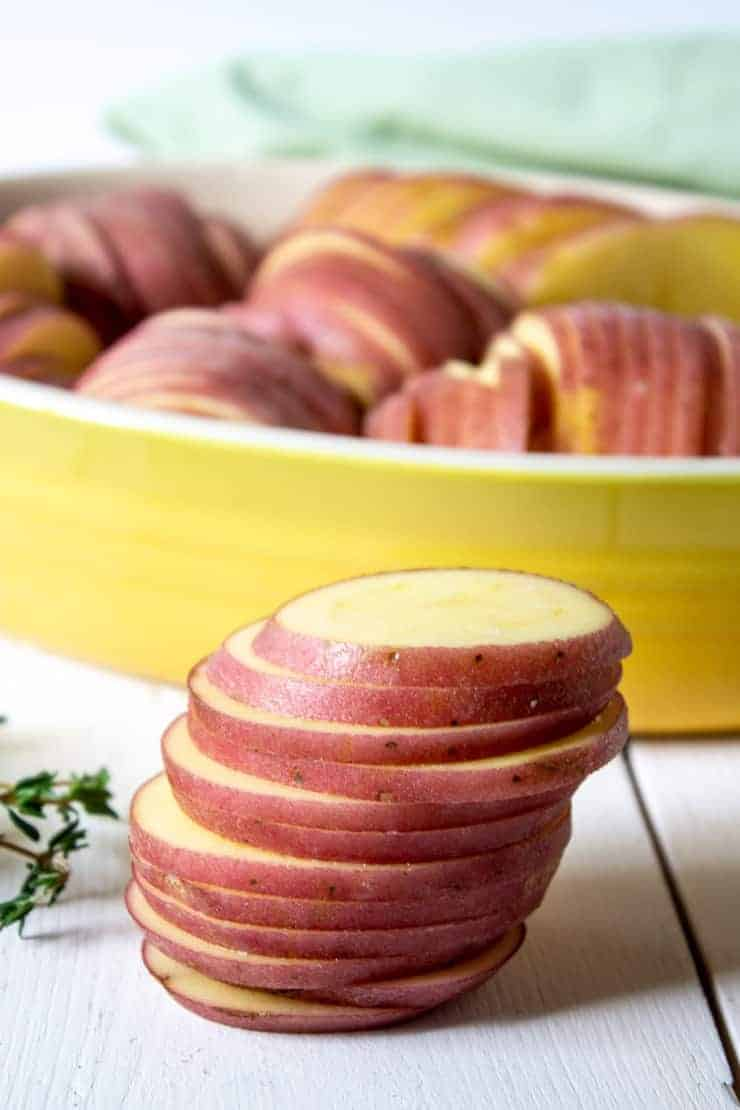 A stack of sliced red potato for roasted hasselback potatoes.
