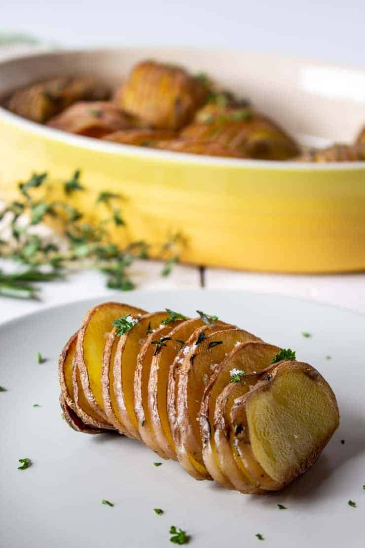 Plated Roasted Hasselback Potatoes with a fresh thyme, rosemary and salt.