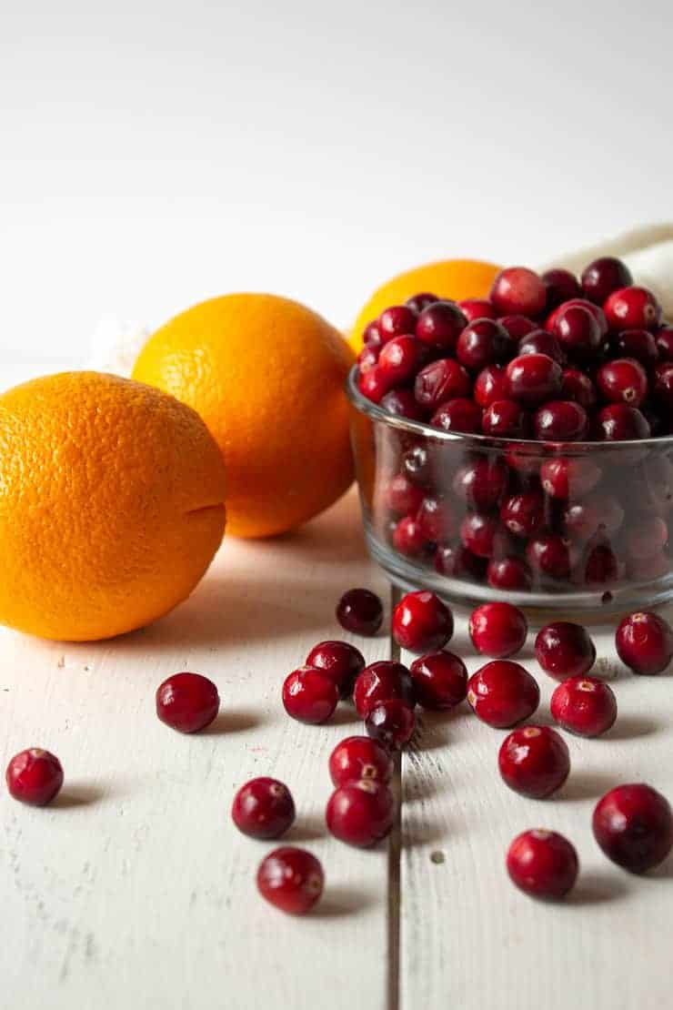 Fresh cranberries and oranges on a white board.