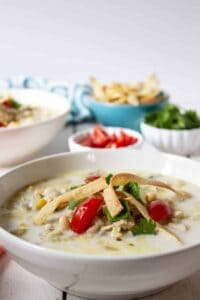 A bowl of white chicken chili topped with tomatoes, cilantro and crispy tortilla strips.
