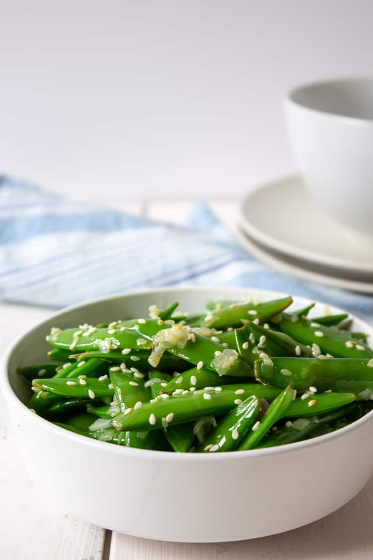 A bowl full of sauteed sugar snap peas topped with sesame seeds.