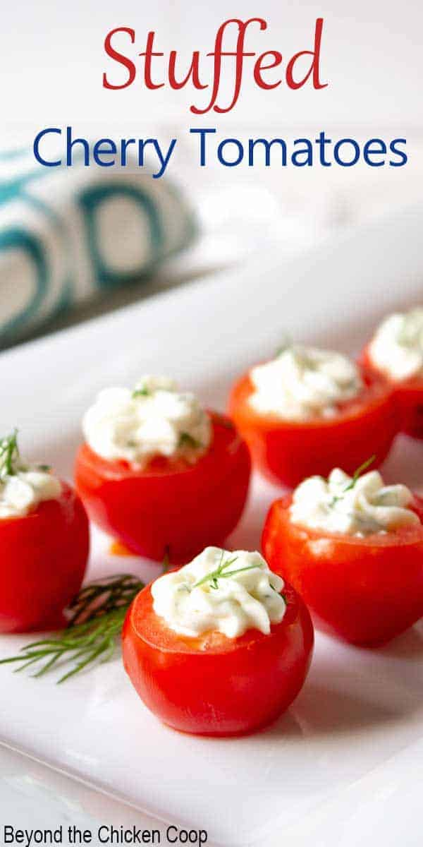 Cherry tomatoes stuffed with cream cheese and herbs on a long white plate.