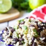 A colorful bowl filled with black beans, rice and herbs.