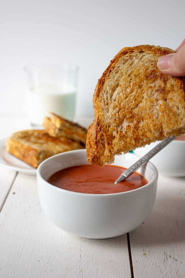 A crispy grilled cheese sandwich and a bowl of creamy tomato soup.