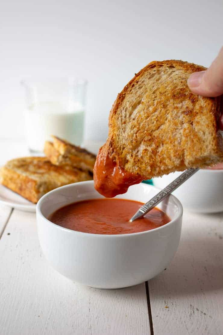 A grilled cheese sandwich dipped into creamy tomato soup.