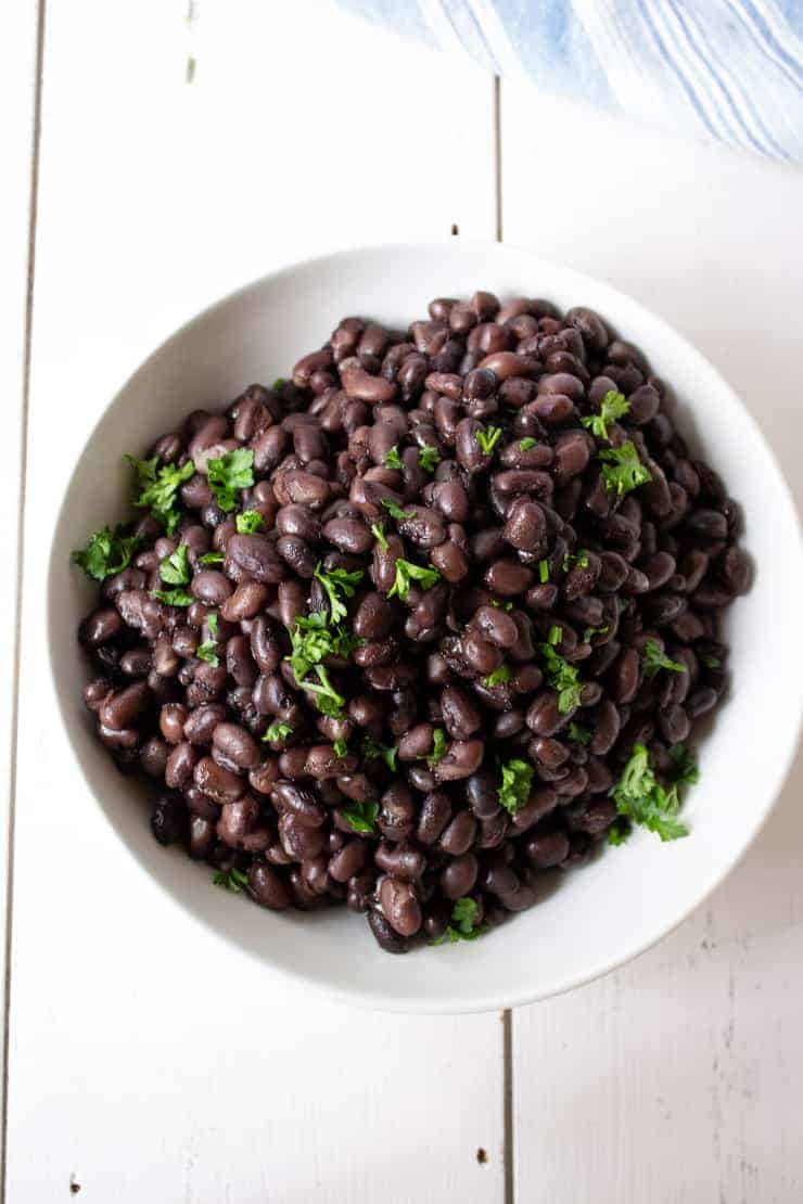 A bowlful of black beans cooked in a pressure cooker.
