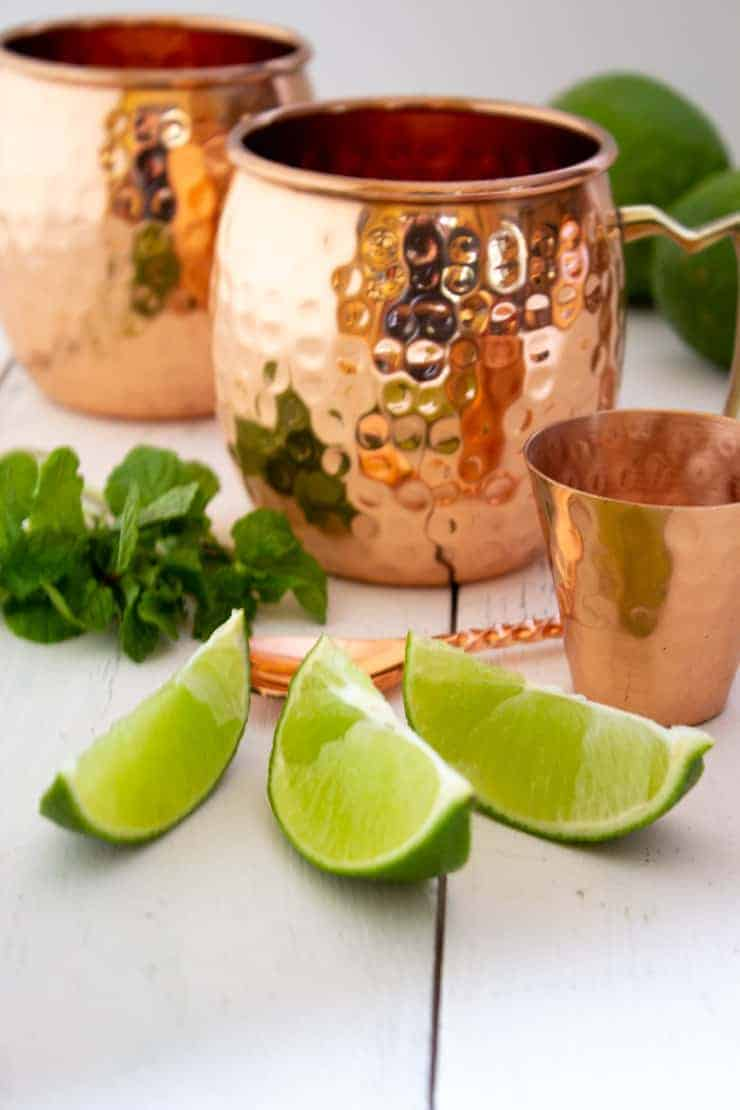 Fresh cut limes and mint for in front of Moscow Mule mugs.