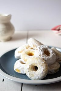 Baked donuts dipped in powdered sugar.