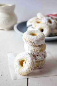 A stack of powdered sugar donuts.