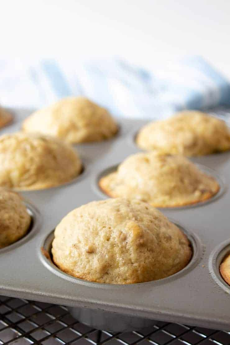 Cooked muffins in a baking tin.