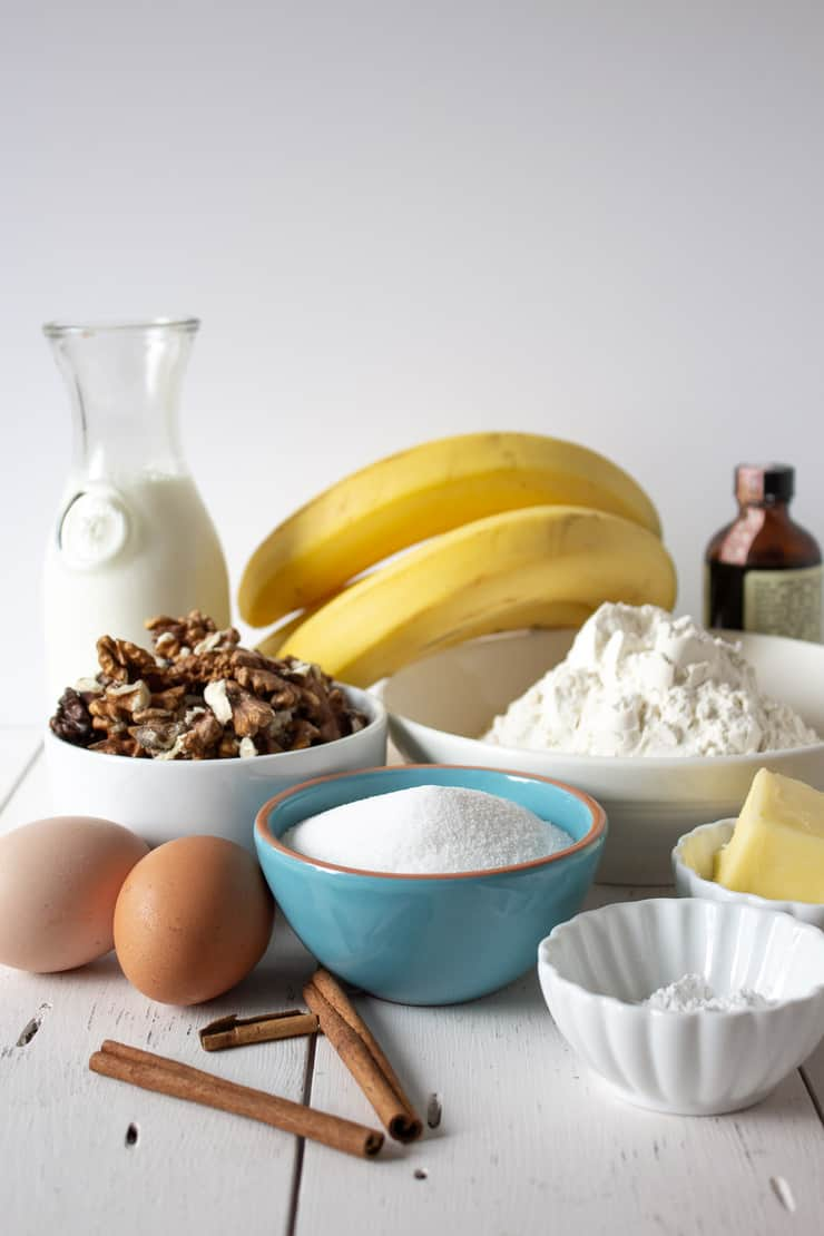 A arrangement of bananas, cinnamon sticks, eggs, walnuts, sugar, flour and other ingredients.