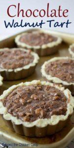 Mini Chocolate Walnut Tarts on a baking tray.