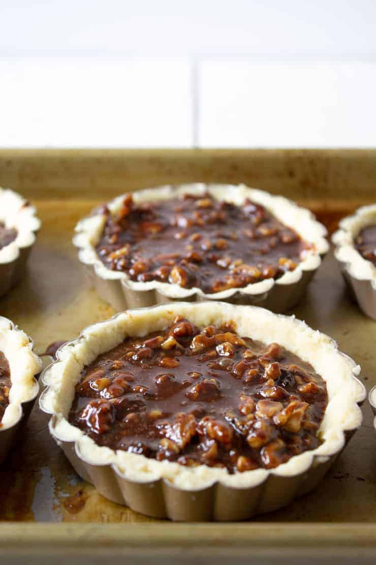 Tart crusts filled with a chocolate walnut filling.