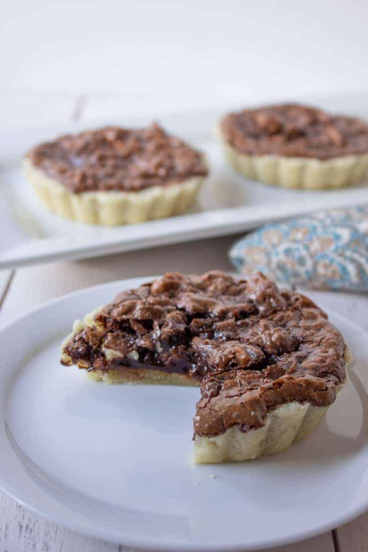 A mini chocolate walnut tart with a slice missing.